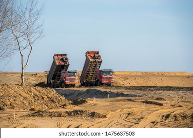 dump truck unloading sand Two red dump trucks unload the soil