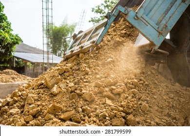 Dump truck unloading soil at construction site