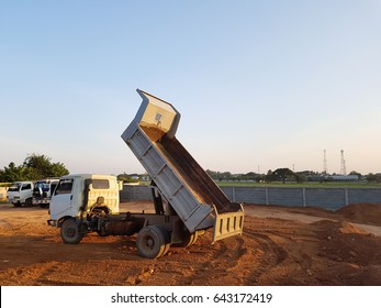 Dump truck unloading soil or sand at construction site during road worksDump truck unloading soil or sand at construction site during road works