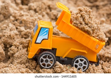 Dump truck unloads soil on the sand at a construction site