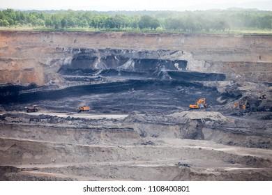 Dump trucks and excavator working at coal mine