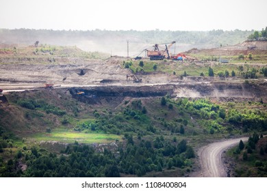 Dump trucks and excavators working at open coal mine