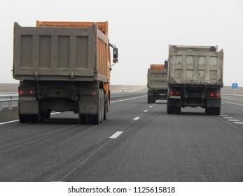 Dump trucks on the road. Mangistau region. Kazakhstan.