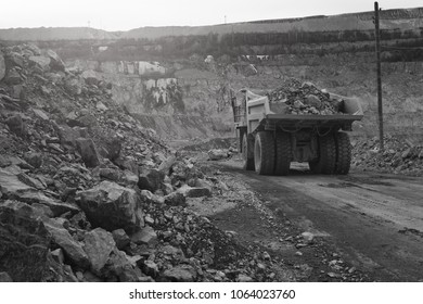 Dump-body truck loaded with ore moves along the road in a quarry, back view, black and white. Mining industry. Mine and quarry equipment.
