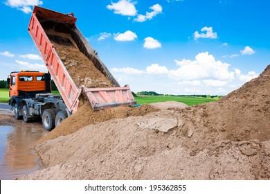 Dumper truck unloading soil or sand at construction site during road works at blue sky background