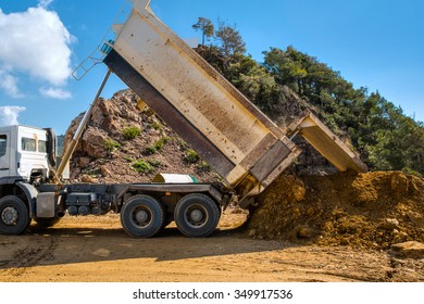 Dumper truck unloading soil or sand at construction site during road works
