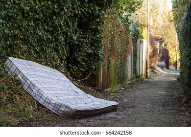 Dumping rubbish, mattress in the streets on a pathway near a park, people littering and dumping rubbish
