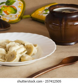 Dumpings and parsley - russian pelmeni with meat. Cook dumplings. Pot and spoon. Baking.