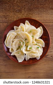 Dumplings, filled with mashed potato in plate on wooden table. Varenyky, vareniki, pierogi, pyrohy - dumplings with filling. Vegetarian dish. overhead, vertical