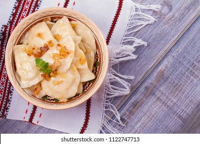 Dumplings, filled with mashed potato - vegetarian dish. Varenyky, vareniki, pierogi, pyrohy in a bowl on wooden table. overhead, horizontal