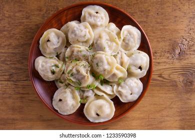 Dumplings, filled with meat, ravioli. Traditional Russian dish pelmeni. Dumplings with filling. View from above, top studio shot
