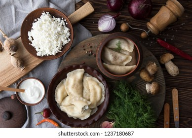 Dumplings, ingredients and spices on wooden table. Russian and Ukrainian cuisine. top view