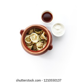 Dumplings with Minced Meat also known as Pelmeni, Gyoza, Dim Sum, Jiaozi, Momo, Tortellini, Pierogi, Varenyky, Mandu or Ravioli in Rustic Clay Ceramic Pot With Sauce and Sour Cream on White Background