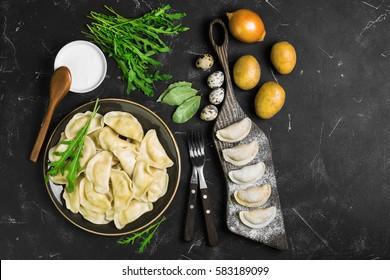 Dumplings with potatoes in plate on black background. On board cooking raw dumplings with potatoes. Ingredients for dumplings onions, arugula, eggs, bay leaf, potatoes, sour cream sauce. Top view.
