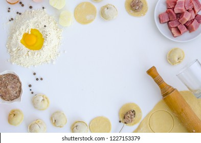 Dumplings raw on white table. Traditional homemade food. The process of cooking dumplings. Pierogi, pelmeni, ravioli with meat. Pepper mill, pepper, onions, meat, egg. Flat lay, mockup, hero header