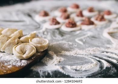 Dumplings raw on a wooden board. Traditional homemade food. The process of cooking dumplings. Traditional pierogi, pelmeni, ravioli, dumplings with meat.