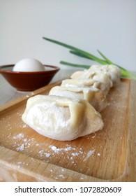 Dumplings raw on a wooden plate