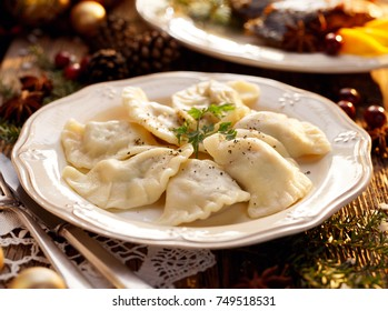 Dumplings stuffed with mushroom and cabbage on a white plate on wooden table.Traditional Christmas eve dish in Poland