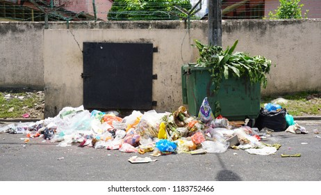 Dumpster bin overflowing with garbage on the sidewalk