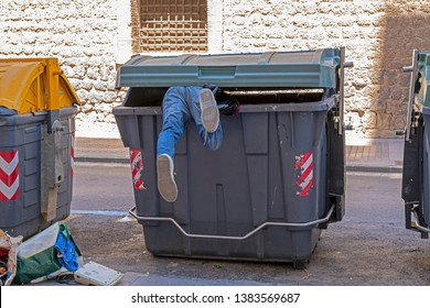 Dumpster diving: man in denim jeans climbs into a large green rubbish (trash) bin in the street; just his feet are sticking out. He retrieves items of perceived value to use or sell  for profit.