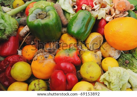 A dumpster full of rotten fruit and vegetables outside a supermarket.