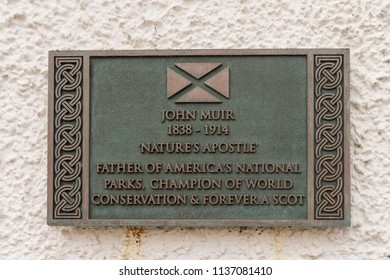"DUNBAR, SCOTLAND - JULY 17, 2018: Sign at the John Muir birthplace building in Dunbar, Scotland.  John Muir was known as ""Father of the National Parks"" in the USA."