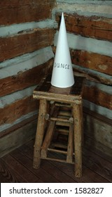 A dunce cap sitting on a stool in the corner of an old schoolhouse.