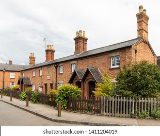 Dunchurch, Warwickshire / UK - May 29th 2019: A row of six brick-built, Grade II listed, almshouses with small gardens behind a picket fence.