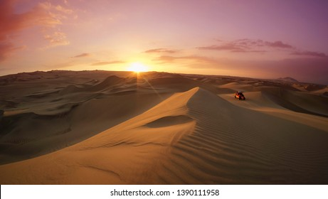 Dune buggy at the desert at sunset hour. Huacachina, Ica, Peru. Extreme sports, adventure and travel concept. Wide angle shot.