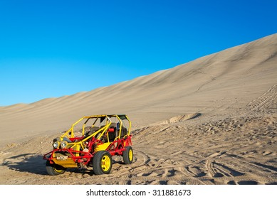 Dune buggy at the foot of a large sand dune in Huacachina, Peru