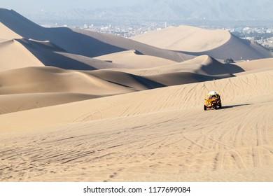 Dune buggy rides the sand dunes in Huacachina desert, Peru