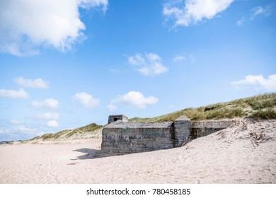 Dune on a beach with ruins of 2nd world war bunkers in the summer under a blue sky