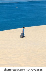 Dune of Pilat, France - September 10,2018: A lonely tourist with a suitcase on the Dune of Pilat, the tallest sand dune in Europe. La Teste-de-Buch, Arcachon Bay, Aquitaine, France