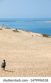Dune of Pilat, France - September 10,2018: Woman on the Dune of Pilat, the tallest sand dune in Europe. La Teste-de-Buch, Arcachon Bay, Aquitaine, France