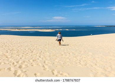 Dune of Pilat, France - September 10,2018: Woman on the Dune of Pilat, the tallest sand dune in Europe. La Teste-de-Buch, Arcachon Bay, Aquitaine, France