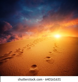 dune and sunset sky, footsteps on  sand in sun light