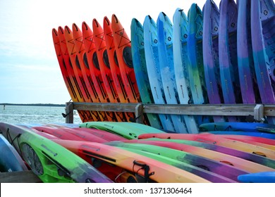 Dunedin, Florida / USA - April 14th 2019; Colorful collection of orange, blue, green, red  and purple rental kayaks stored upright and laying on beautiful beach on a sunny breezy spring day