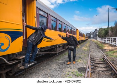 Dunedin , New Zealand - December 18th, 2017 :  Cheerful young girl posing with her father in front of a historic train during on her graduation  trip in Dunedin, New Zealand
