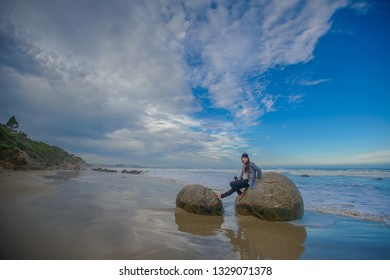 Dunedin , New Zealand, Feb 10th, 2019: tourist sit at Spheric Moeraki Boulders stone on the Koekohe beach, Landmark on the east coast of the South Island