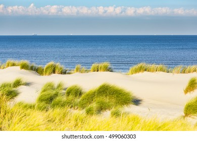 dunes, clouds, sea and a blue sky
