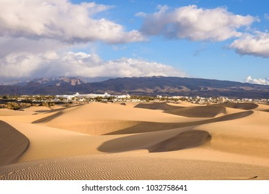 Dunes in Maspalomas, Gran Canaria. Sunrise in sand dunes (El Oasis) on beach Playa del Ingles of Maspalomas with mountains and resorts in background.