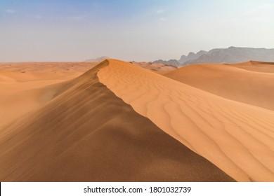 Dunes and wind. Flying sand. Dubai Desert.