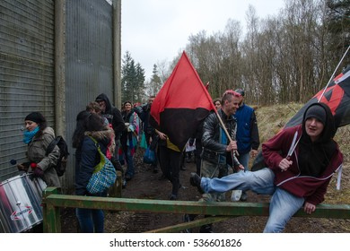 DUNGAVEL DETENTION CENTRE, STRATHAVEN, SCOTLAND, 7TH MAY 2016 - Activists with anarchists flags walking around and over a vehicle barrier outside the detention centre fence