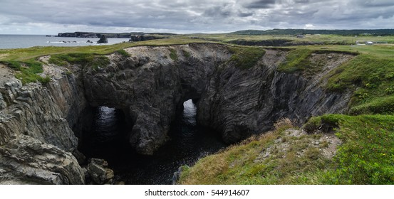 Dungeon national Park, Newfoundland featuring a rare natural occurrence of rock formation under which, two tunnels comprise a haunting face - earning it its local nickname, Devil's eyes.