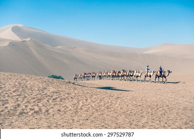 DUNGHUAN, CHINA â?? JUNE 29: Camel train at the famous singing sand dunes of the Gobi desert on June 29, 2012 in Dunhuang. The sand dunes in Dunhuang on the Silk road are a major tourist attraction.