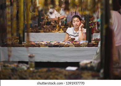 Dunhuang, China - 08 06 2016: A chinese craftswoman selling souvenirs at Shazhou Market, a night market in Dunhuang