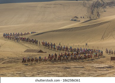 DUNHUANG, CHINA - AUGUST 21, 2018: Tourists ride camels at Singing Sands Dune near Dunhuang, Gansu Province, China