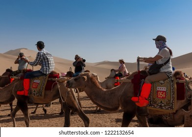 Dunhuang, China - August 8, 2012: Group of Chinese tourists riding camels at the Echoing Sand Mountain near the city of Dunhuang, in the Gansu Province, China.