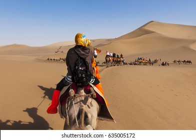 Dunhuang, China - August 8, 2012: Tourists on a camel caravan in the dunes around the city of Dunhuang, in the ancient Silk Road, in China.