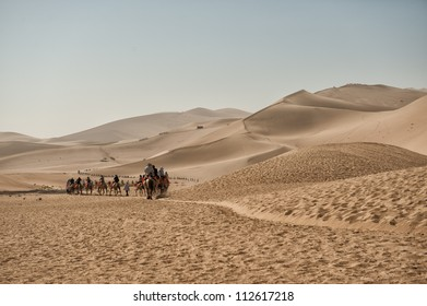 DUNHUANG, CHINA - JUNE 29: Camel safari takes tourists across the famous Mingsha sand dunes on June 29, 2012 outside Dunhuang in the Gobi desert. Dunhuang is located on the historic Silk road.